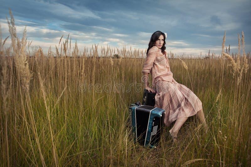 La retro donna sta sedendosi nel campo fotografia stock