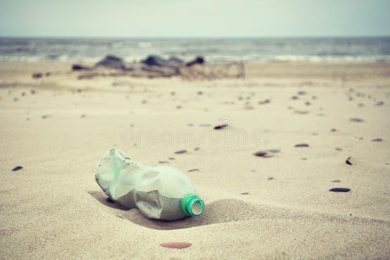 La retro immagine stilizzata di una bottiglia di plastica vuota ha andato su un beac fotografia stock