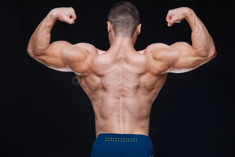 La retrovisione del giovane muscolare in buona salute con le armi ha piegato fuori su fondo nero fotografia stock libera da diritti