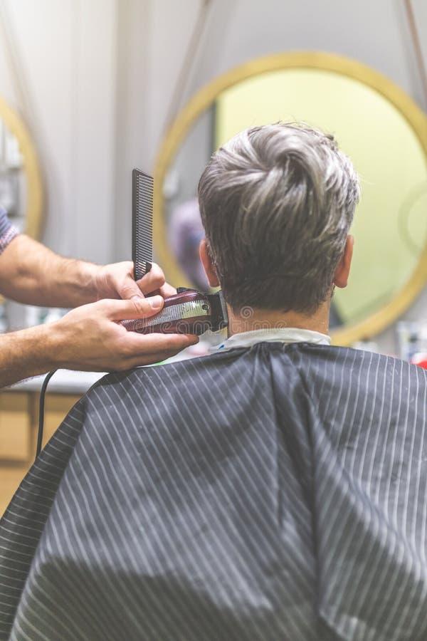 La retrovisione del parrucchiere fa l'acconciatura con la tosatrice ed il pettine fotografia stock libera da diritti