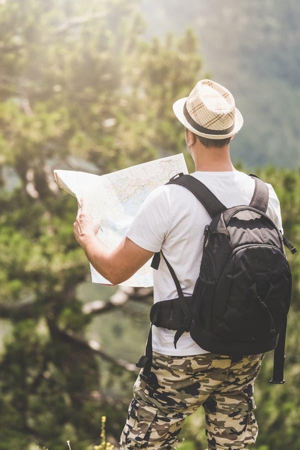 La retrovisione di giovane turista con la tenuta del cappello e dello zaino traccia in natura fotografia stock libera da diritti