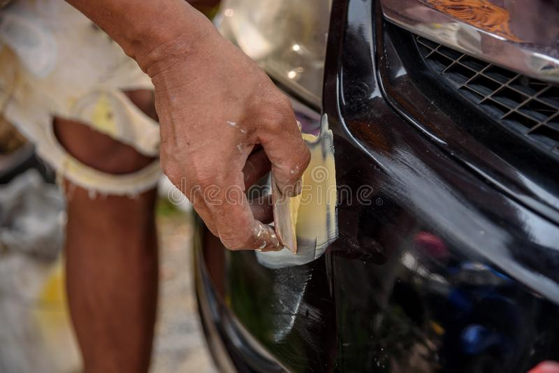 la riparazione del riparatore del lavoratore del meccanico ha graffiato sulla carrozzeria e sul prepa fotografia stock