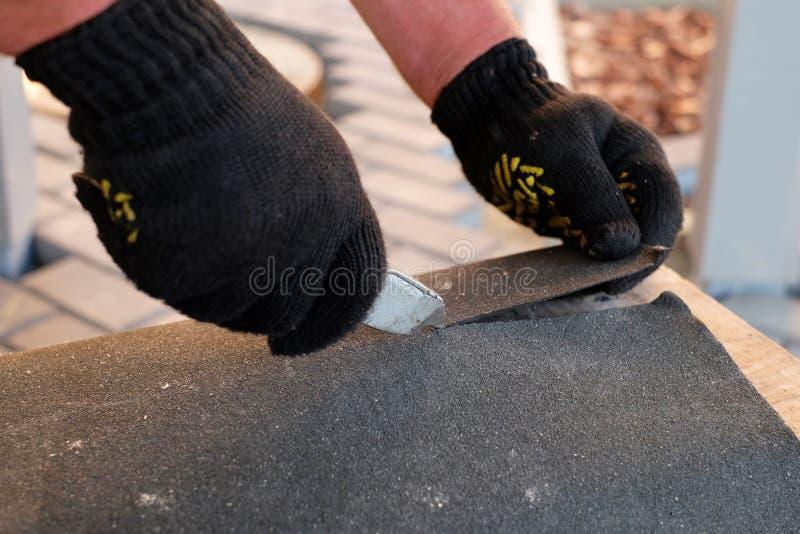 La riparazione del tetto tagliando il feltro per l'installazione delle assicelle del bitume durante l'impermeabilizzazione funzio immagine stock