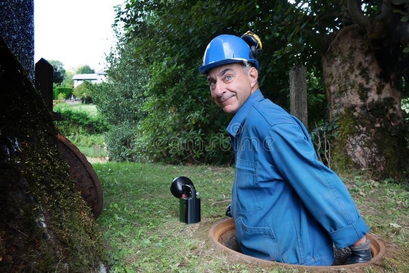 La riparazione della fogna funziona nella botola da un lavoratore immagini stock libere da diritti
