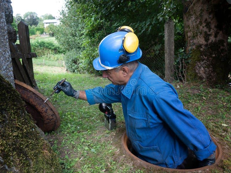 La riparazione della fogna funziona nella botola da un lavoratore immagine stock