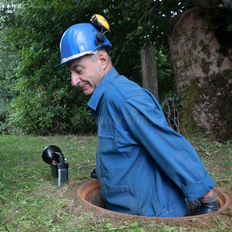 La riparazione della fogna funziona nella botola da un lavoratore immagine stock libera da diritti