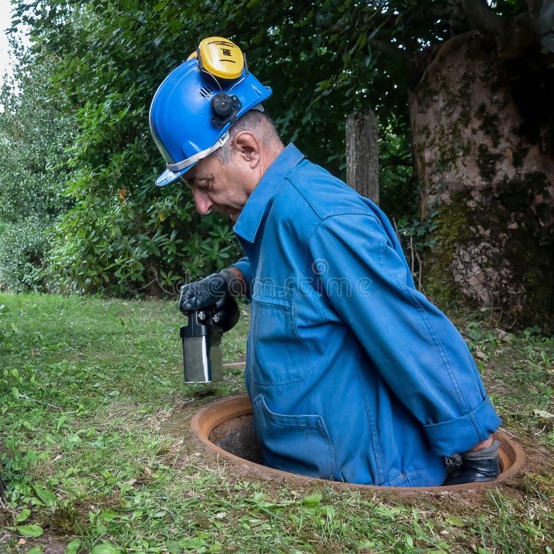 La riparazione della fogna funziona nella botola da un lavoratore fotografia stock