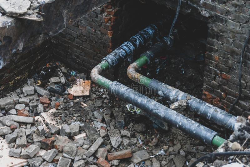 La riparazione delle acque luride, i tubi d'acciaio della fogna o la conduttura in scatola del mattone si sono aperti per la prev fotografia stock