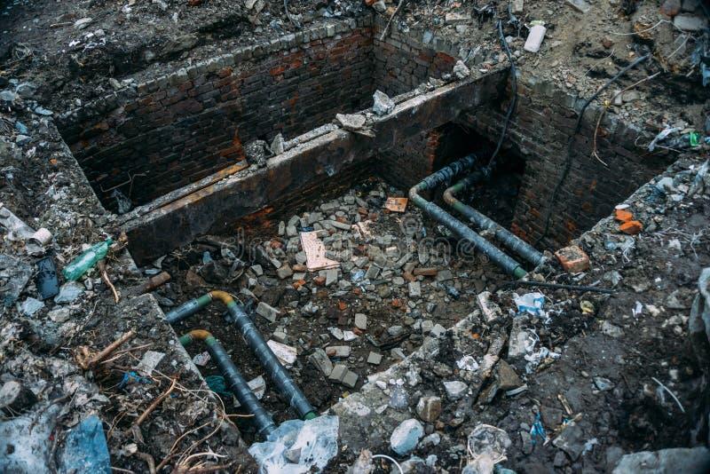La riparazione delle acque luride, i tubi d'acciaio della fogna o la conduttura in scatola del mattone si sono aperti per la prev immagine stock