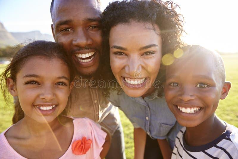 La risa de la familia negra al aire libre, cerca para arriba, detrás encendió el retrato imagenes de archivo