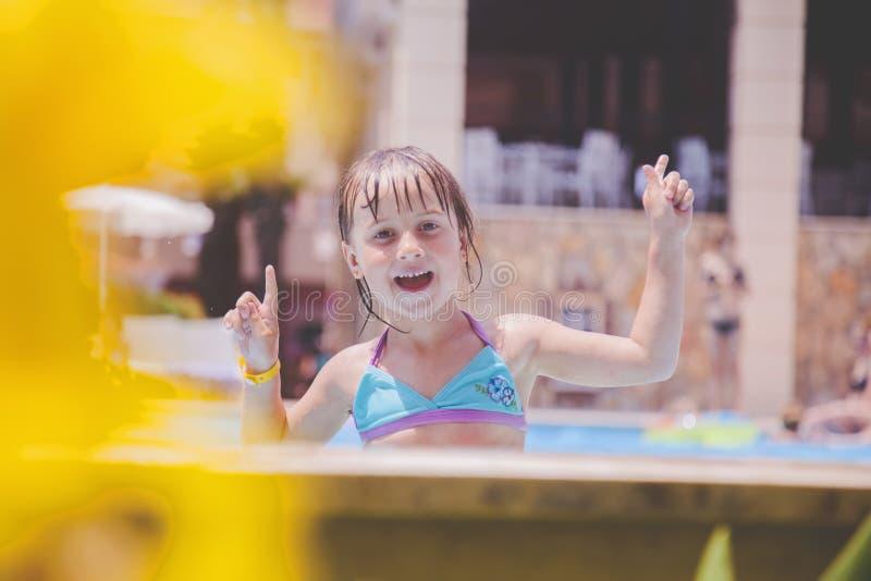 La risa es el indicador más grande de la felicidad de un niño Niña feliz que juega en agua al aire libre en la piscina fotos de archivo libres de regalías