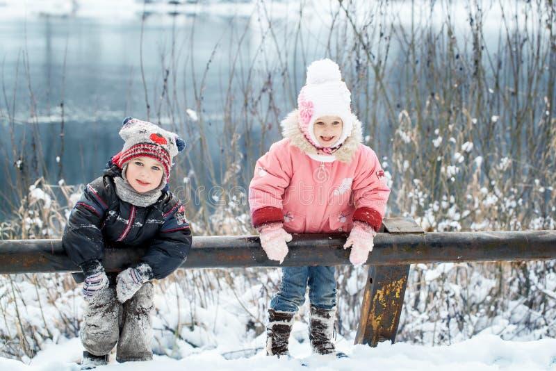 La risa feliz embroma en un bosque nevoso hermoso del invierno imagenes de archivo