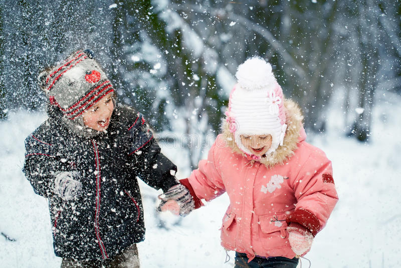 La risa feliz embroma en un bosque nevoso hermoso del invierno fotos de archivo