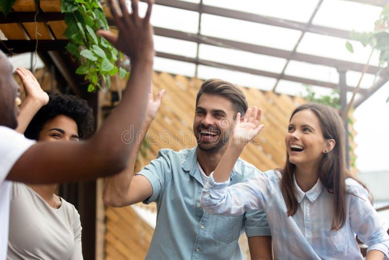 La risa multicultural feliz del grupo de los amigos de la gente joven da altos cinco foto de archivo