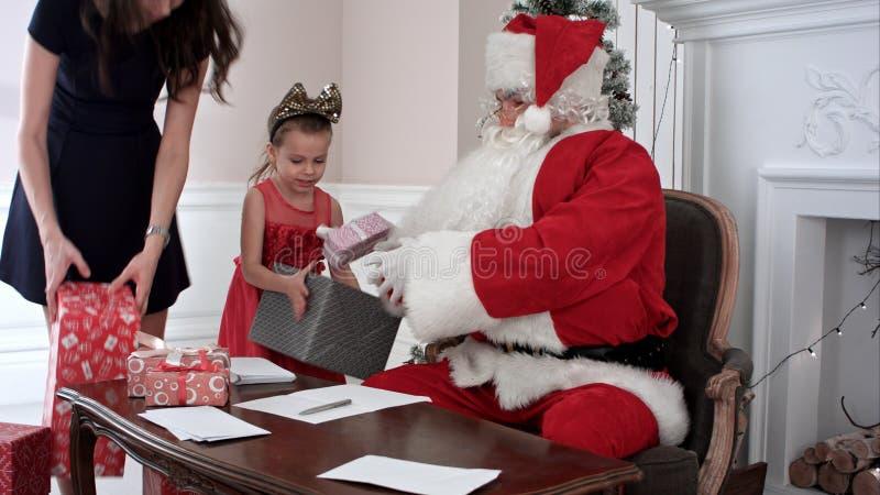 La risposta occupata di Santa chidlren le lettere del ` s mentre assistenti del ` s di Santa i piccoli che portano più presenta fotografie stock libere da diritti