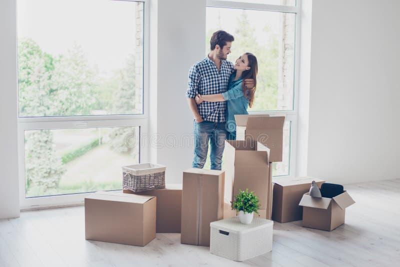 La riuscita giovane coppia sta muovendosi verso il nuovi posto e embracin piacevoli fotografia stock