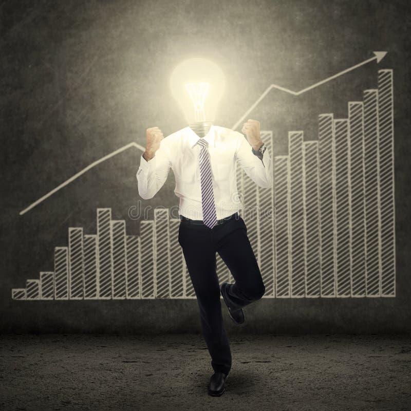 La riuscita lampadina ha diretto l'uomo ed il diagramma di affari immagini stock