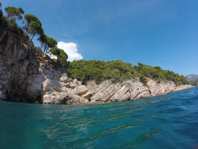 La riva rocciosa, pini si sviluppa sulle rocce, il cielo blu, mare immagine stock libera da diritti