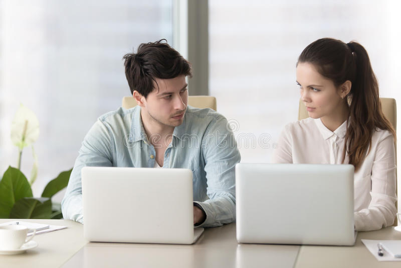 La rivalidad entre los colegas masculinos y femeninos, los compañeros de trabajo enojados mira imagenes de archivo