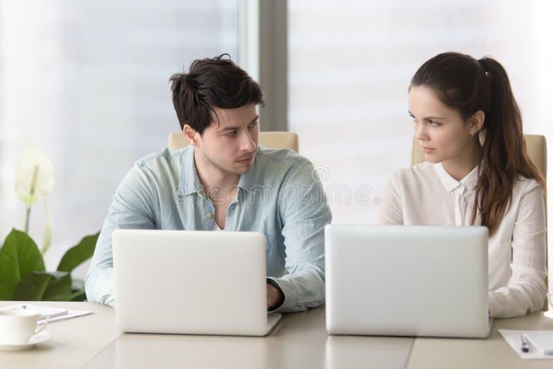 La rivalité entre les collègues masculins et féminins, les collègues fâchés regardent images stock