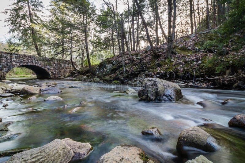 La rivière coule doucement le long des roches près d'un pont en pierre arqué photo libre de droits
