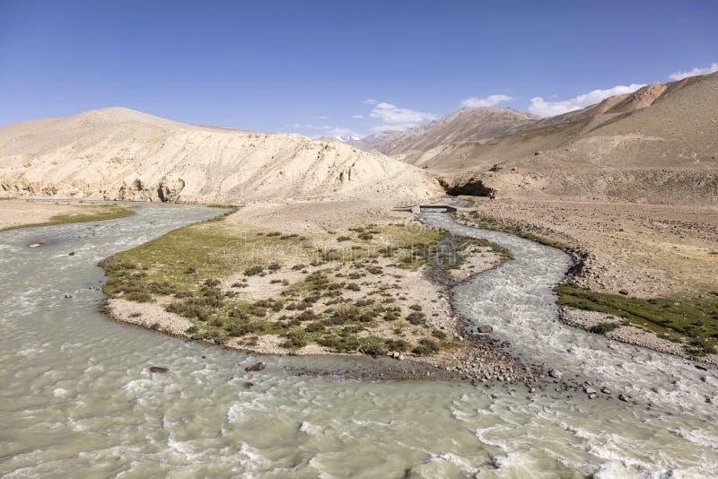 La rivière de Pamir dans les montagnes de Pamir à la frontière entre le Tadjikistan est partie du côté et du côté droit de l'Afgh photographie stock