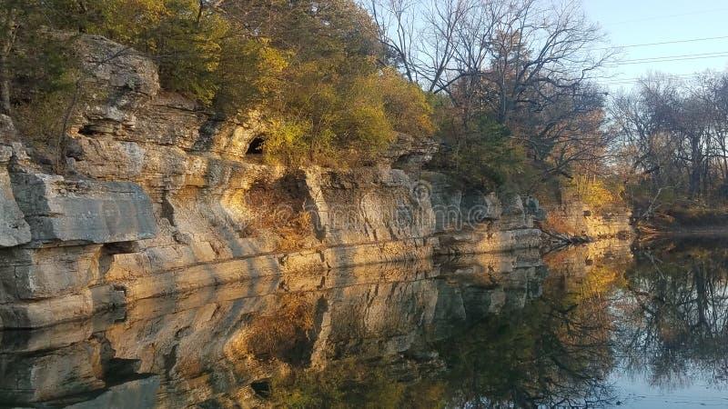 La rivière surplombante de falaise rocheuse se reflète sans problème image libre de droits