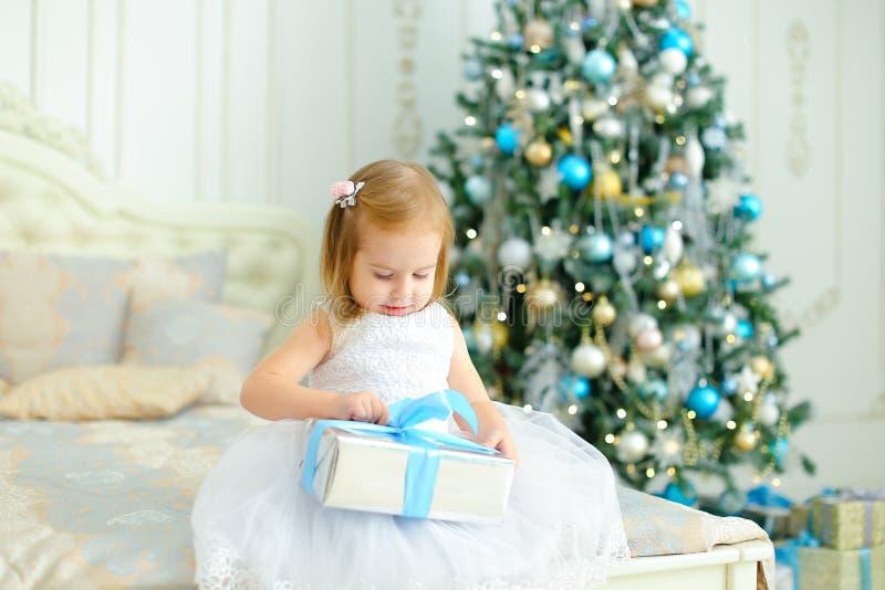 La robe blanche de port de petite fille blonde gardant le cadeau près a décoré l'arbre de Noël dans la chambre à coucher photo stock