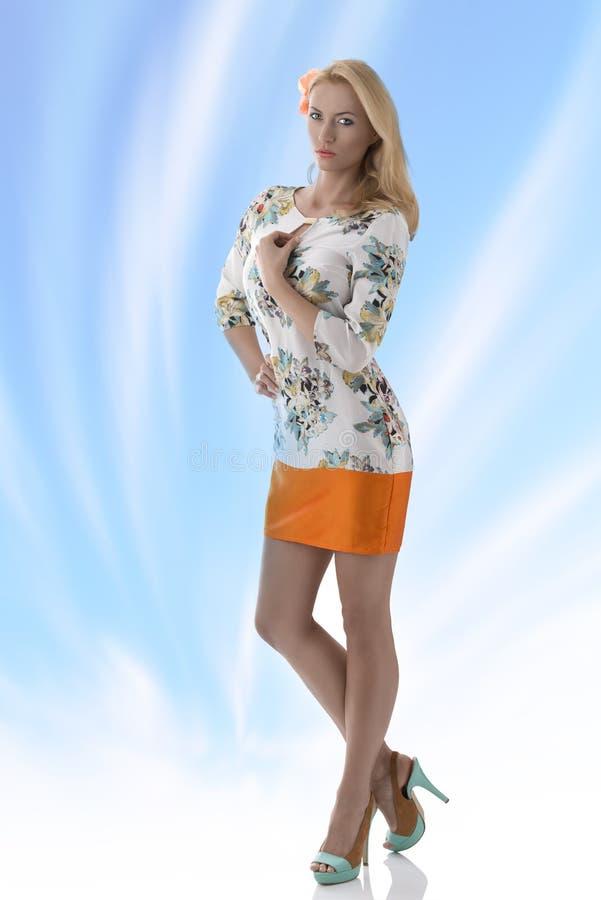 La robe blonde de vêtement de fille avec la configuration florale a eu la main sur le b photo libre de droits