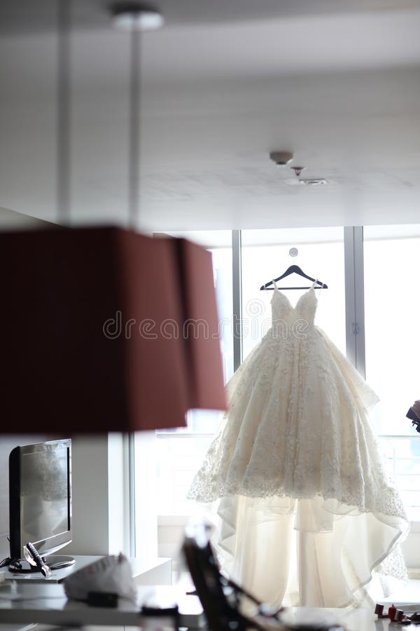 La robe de jeune mariée accrochant sur le mur préparent pour employer le jour de cérémonie l'épousant photographie stock