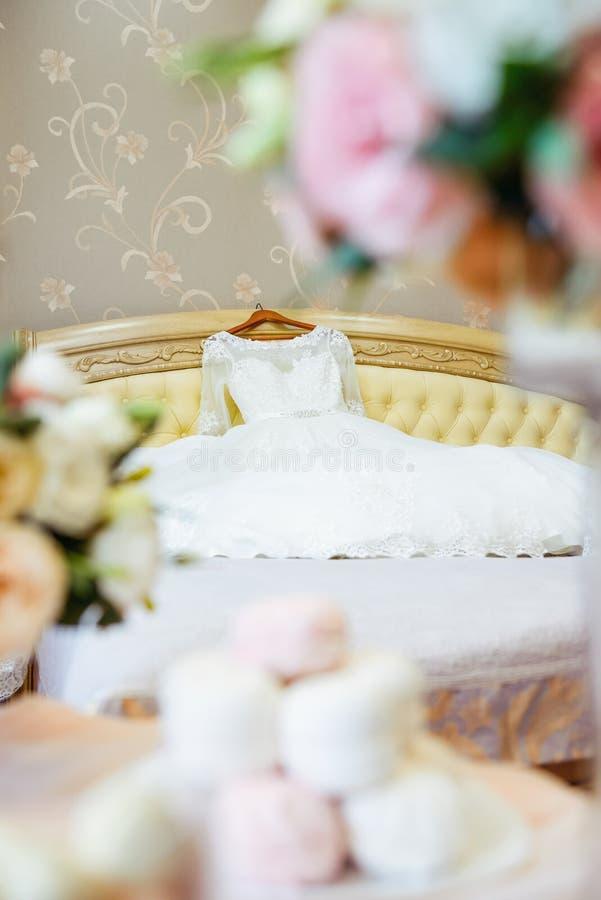 La robe de mariage se trouvant sur le lit et le premier plan brouillé des bonbons à guimauve et le bouquet de l'eustoma fleurit C photographie stock libre de droits
