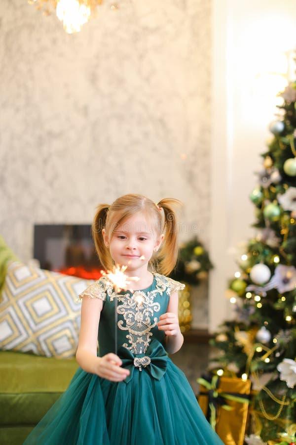 La robe de port et la position de petite gentille fille avec des lumières de Bengale s'approchent de l'arbre de Noël image stock
