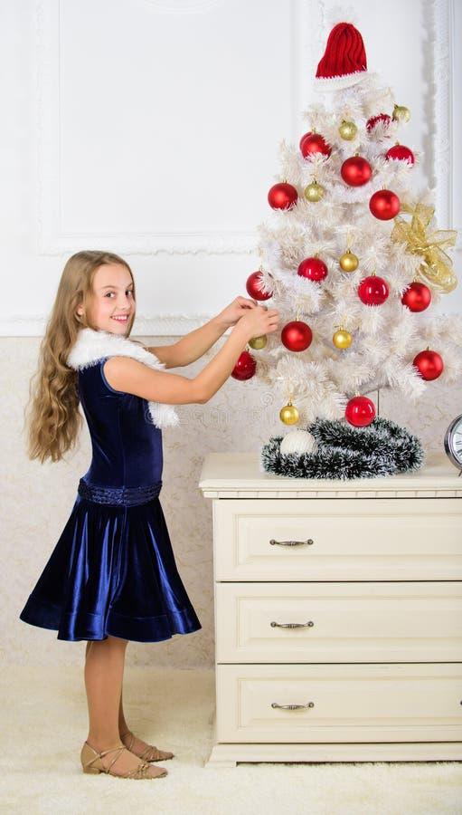 La robe de velours de fille se sentent de fête près de l'arbre de Noël Écartez l'acclamation de Noël Enfant heureux parce que la  photographie stock libre de droits