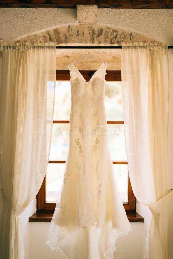 La robe du ` s de jeune mariée accroche sur la corniche photographie stock