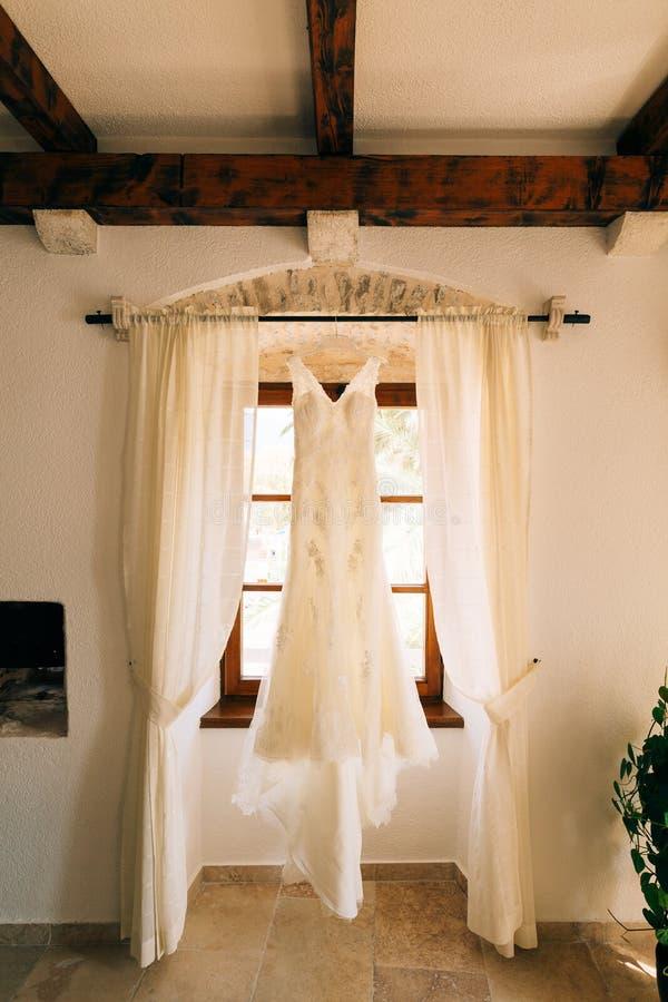 La robe du ` s de jeune mariée accroche sur la corniche photo libre de droits
