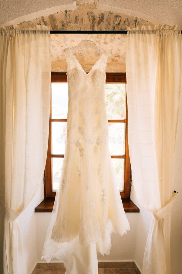 La robe du ` s de jeune mariée accroche sur la corniche photo stock