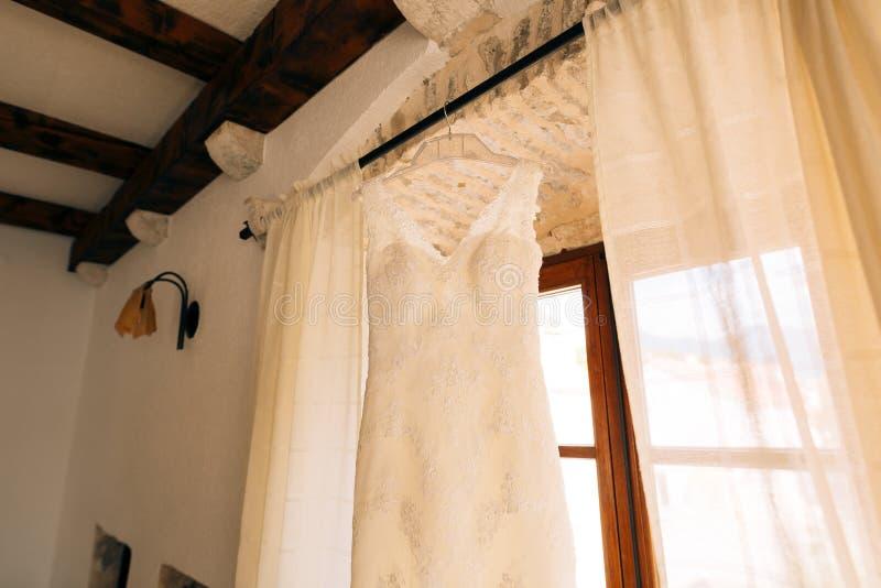 La robe du ` s de jeune mariée accroche sur la corniche image stock