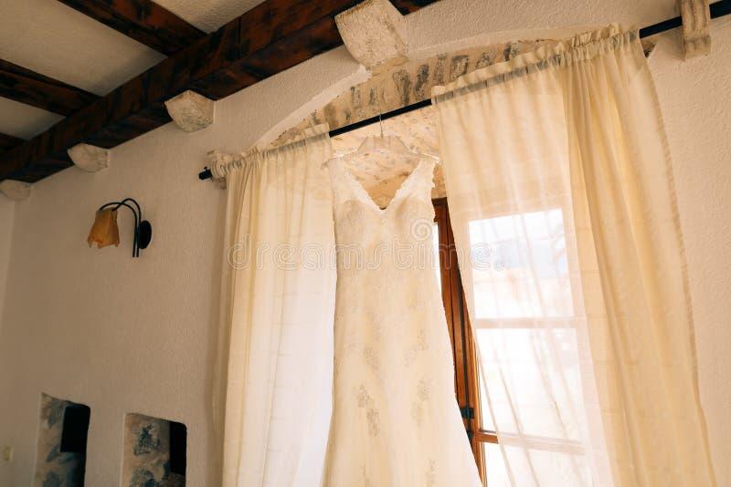 La robe du ` s de jeune mariée accroche sur la corniche images stock