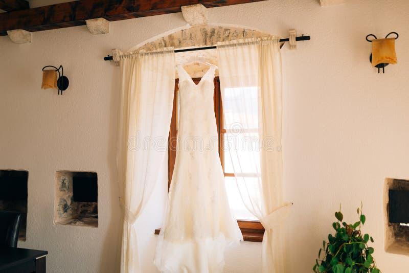 La robe du ` s de jeune mariée accroche sur la corniche photographie stock libre de droits