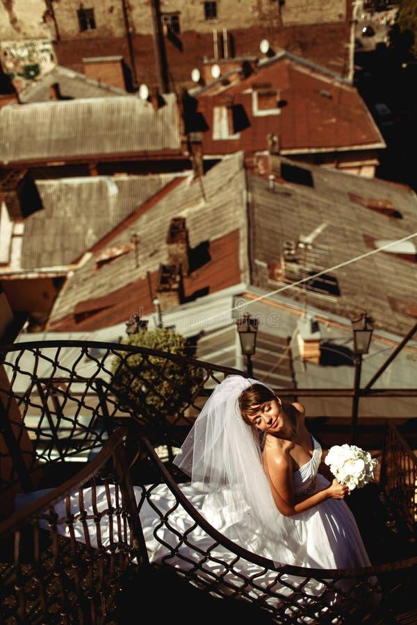 La robe du ` s de jeune mariée se trouve sur les escaliers en spirale tandis qu'elle apprécie le sunshin photo stock