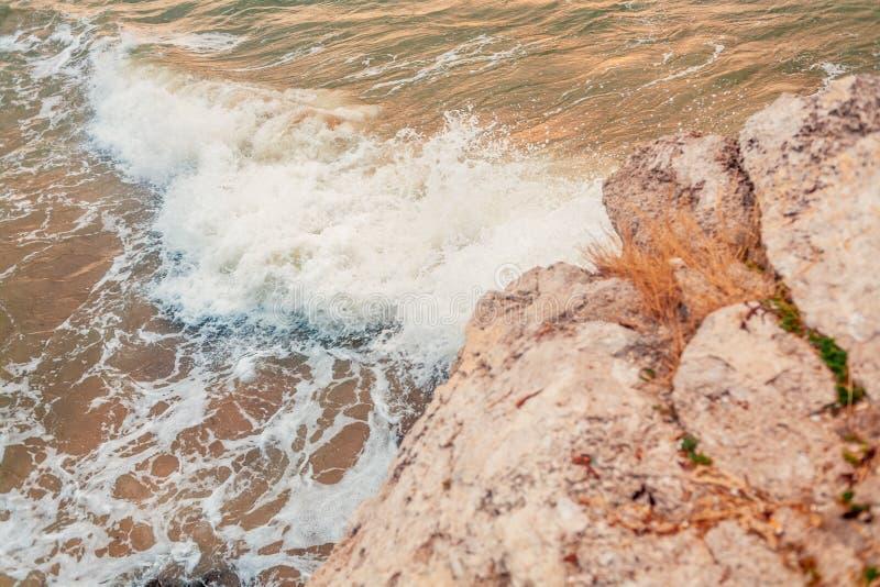 La roca del mar está rompiendo la onda potente con espuma en su top fotografía de archivo