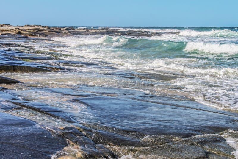 La roche volcanique s'étirant dans un océan turbulent lorsque les vagues s'écrasent à l'horizon avec un petit voilier images libres de droits
