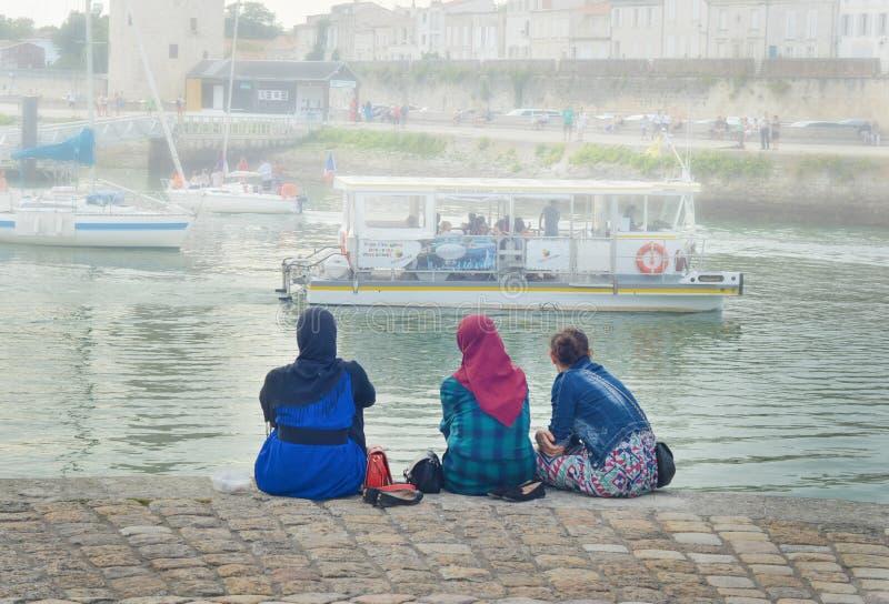 LA ROCHELLE, FRANÇA - 12 DE AGOSTO DE 2015: Hijab vestindo da mulher muçulmana que olha no oceano e nos iate em La Rochelle, Fran fotografia de stock royalty free