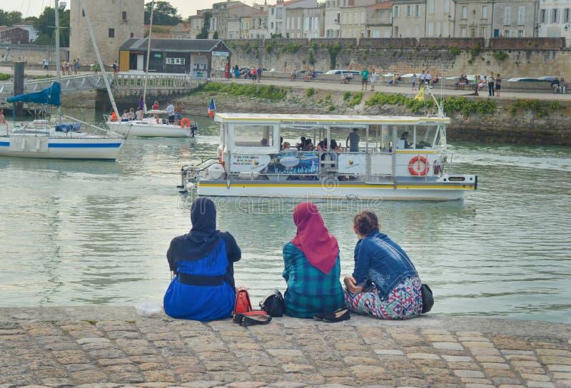 LA ROCHELLE, FRANÇA - 12 DE AGOSTO DE 2015: Hijab vestindo da mulher muçulmana que olha no oceano e nos iate em La Rochelle, Fran imagem de stock
