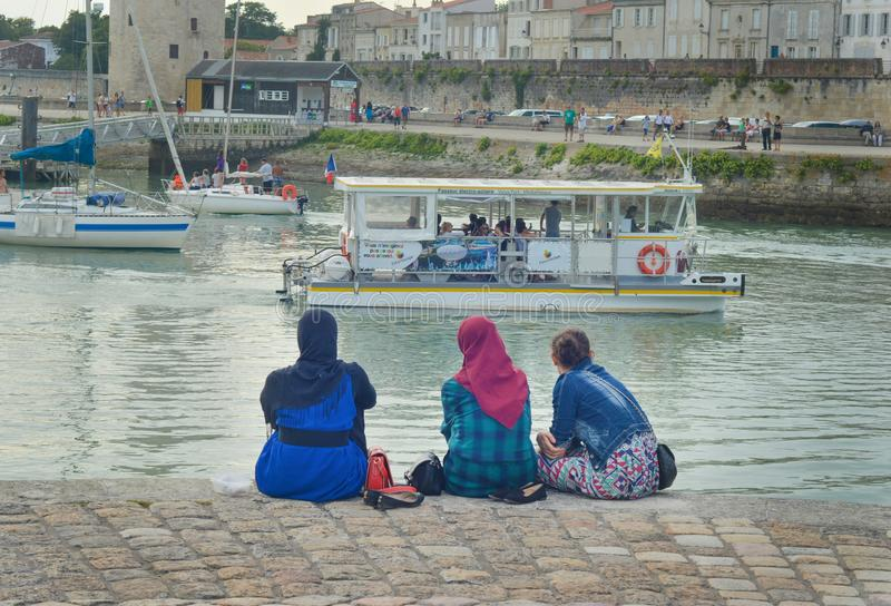 LA ROCHELLE, FRANCE - AUGUST 12, 2015: Muslim woman wearing hijab looking on the ocean and yachts at La Rochelle, France. stock image