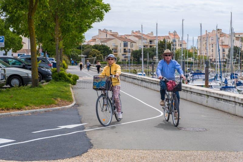 Elderly couple rides on bikes near Port des Minimes in La Rochelle, France. La Rochelle, France - May 07, 2019: Elderly couple rides on bikes near Port des stock photo