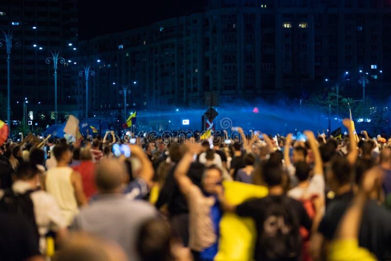 La Romania, Bucarest - 10 agosto 2018: Polizia facendo uso dei canoni dell'acqua per spaccare la folla che protesta anti governo  fotografia stock libera da diritti