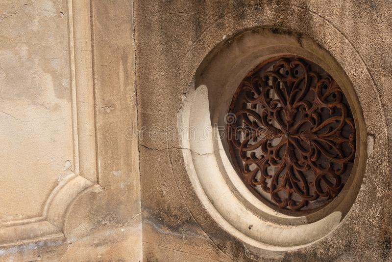 La ronda adornada aherrumbró parrilla del metal fijada en el muro de cemento formado imágenes de archivo libres de regalías