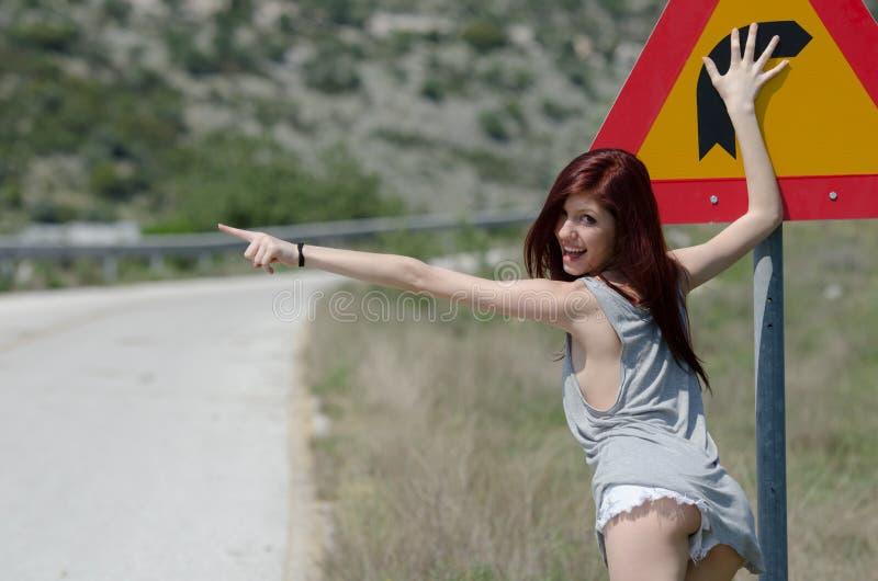 La ropa caliente de la ropa de mujer oculta una vuelta del peligro de la señal de tráfico foto de archivo