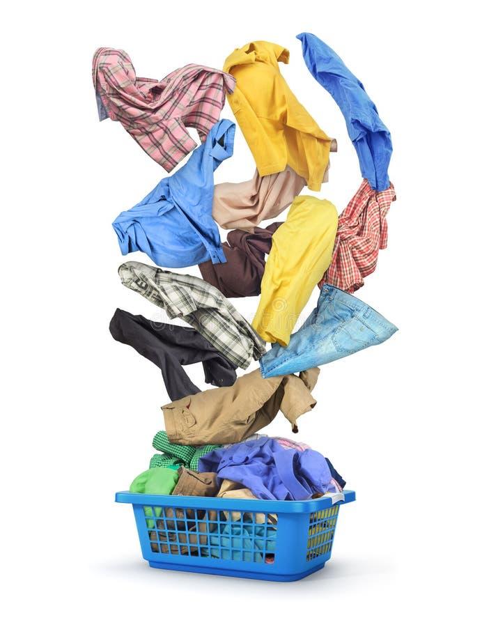 La ropa colorida cae en una cesta de lavadero llena fotografía de archivo libre de regalías